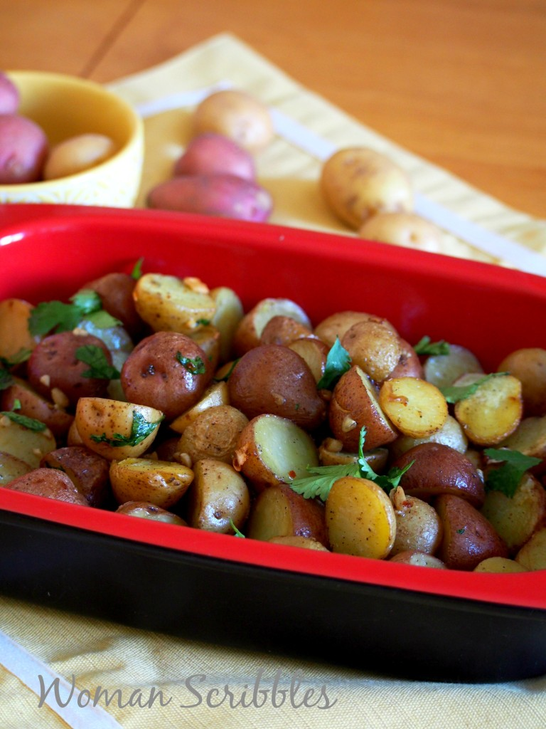 Roasted mini potatoes arranged in a dish and topped with parsley and cilantro.