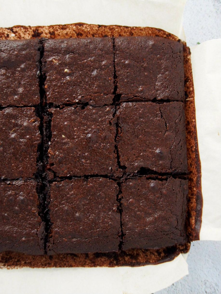 Top view of freshly baked coconut oil brownies cut into squares.