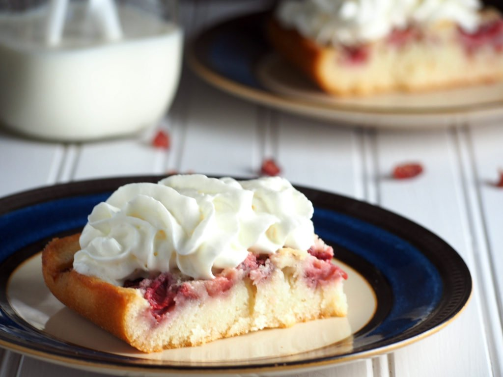 A slice of strawberry cobbler topped with whipping cream.