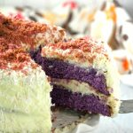 Taking a slice off the ube cake on a serving plate.