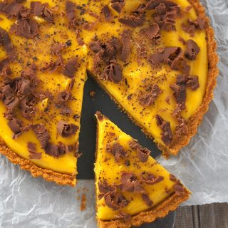 Top shot of mango tart with a slice cut off.