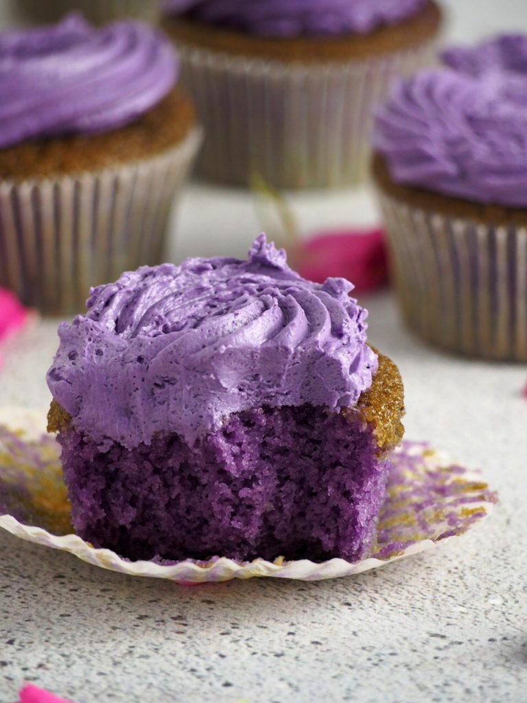Ube cupcake with a bite, showing the inside crumb of cake.