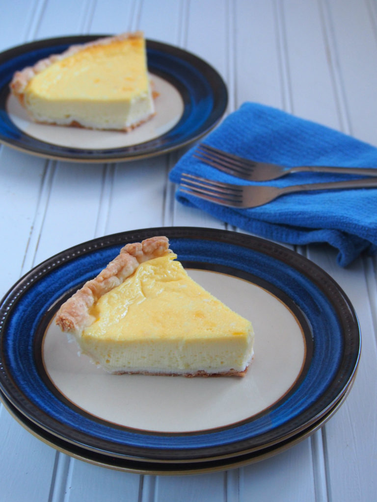 Two saucer plates of egg pie slices served.