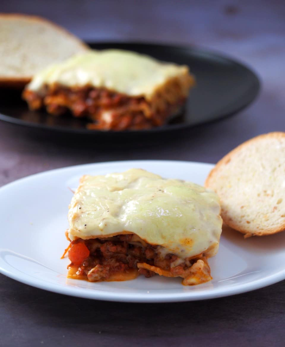 Lasagna slices in serving plates with bread.