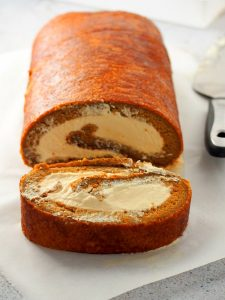 Photo of coffee swiss roll with one cut slice.