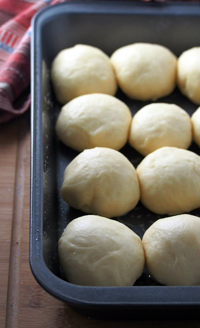 Honey buns dough filled and rising in the pan.
