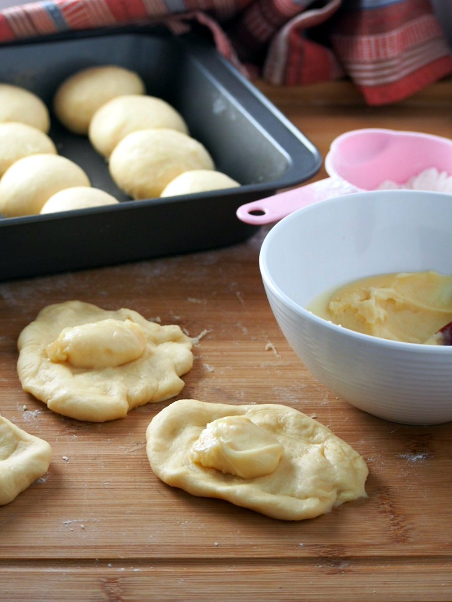 Honey buns dough being filled with the honey cream in the center.