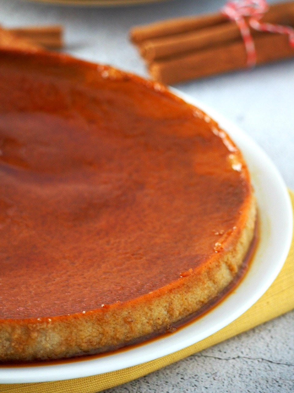 Cinnamon Flan on a big serving plate with its base soaked in caramel syrup.