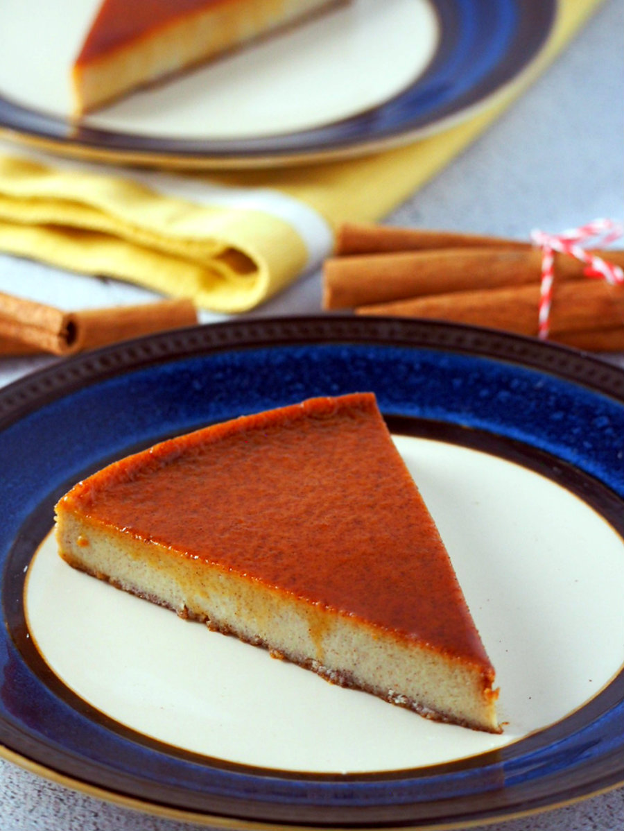 A slice of cinnamon flan on a saucer plate.