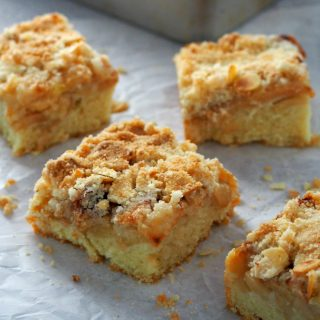Square slices of Apple Streusel Coffee Cake on a big sheet of parchment paper.