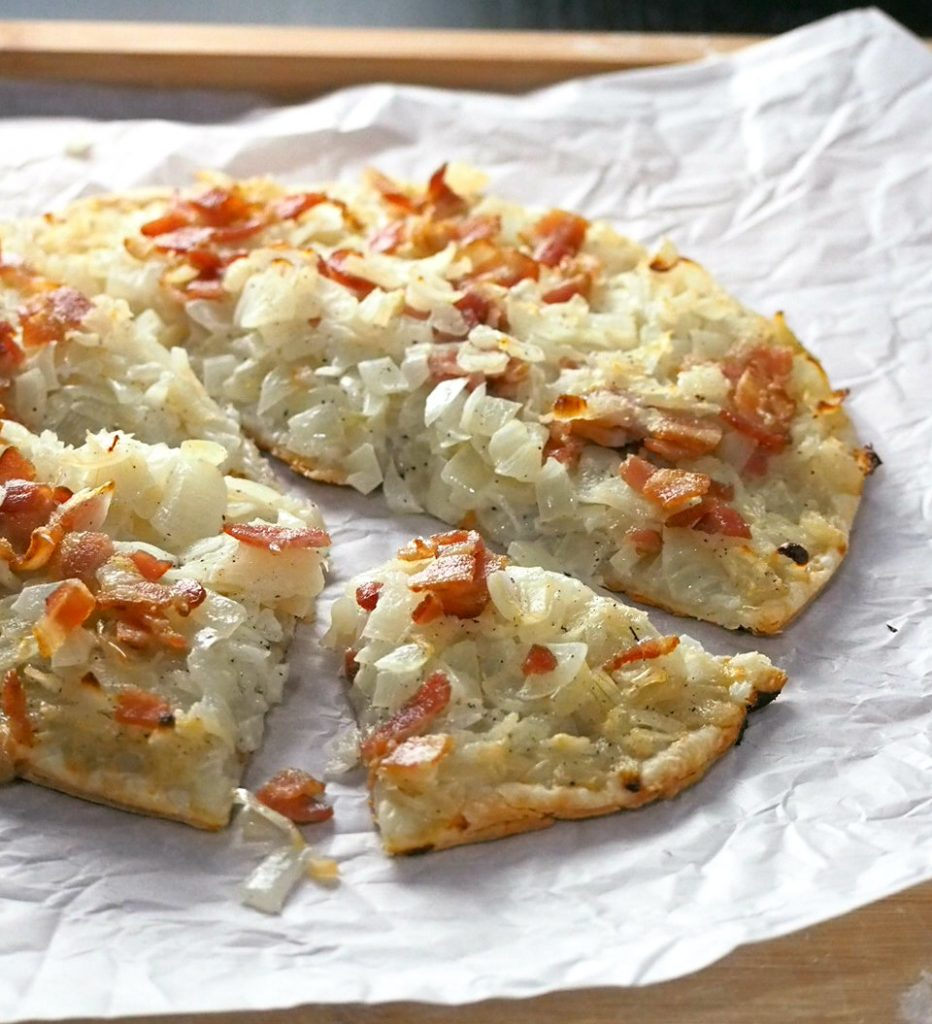 This Onion Tart is a tasty appetizer made with soft, juicy onions piled together with bits of bacon on a crisp and light puff pastry crust.