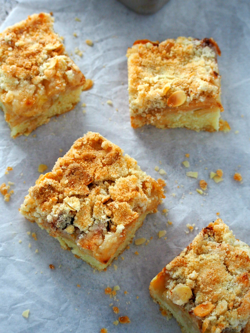 Slices of apple streusel coffee cake laying on a parchment paper, top view.