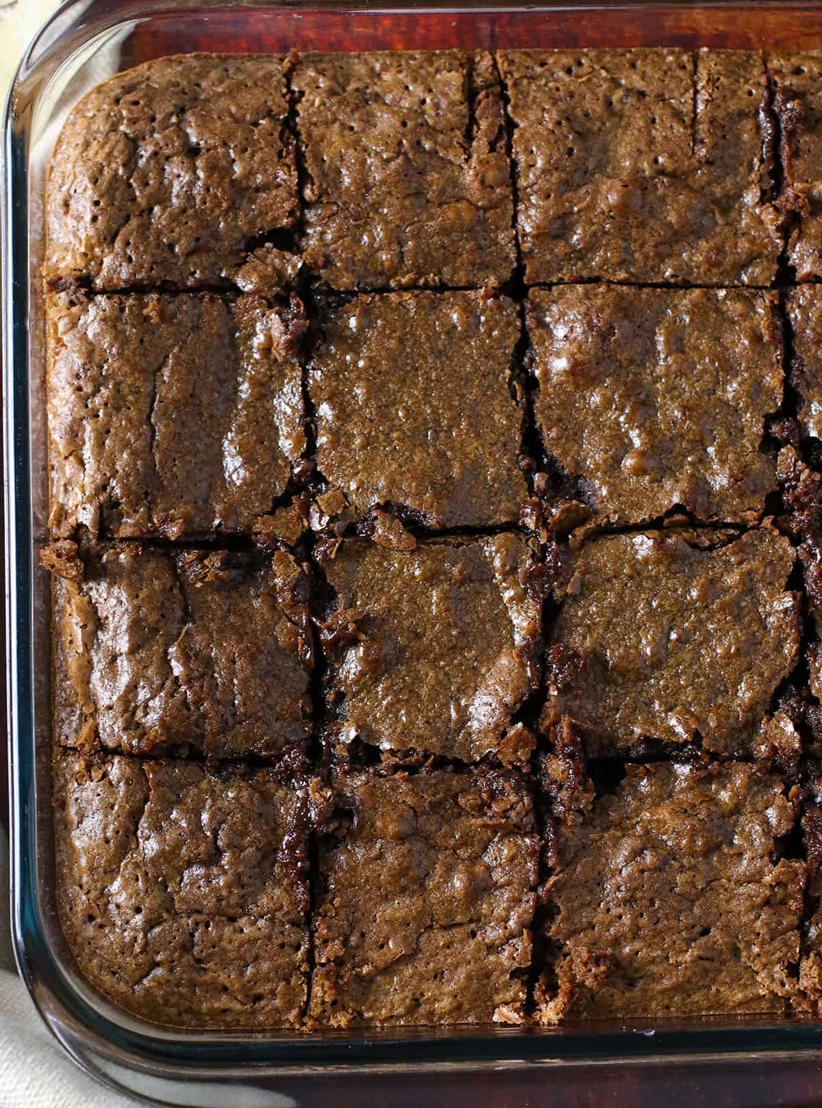 A pan of freshly baked brownies, sliced into squares.