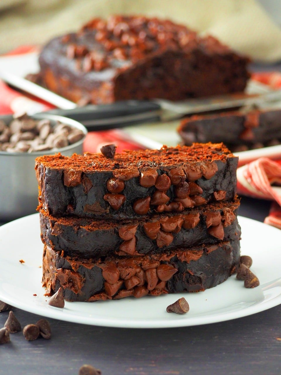 Three slices of pumpkin chocolate bread stacked on a serving plate.