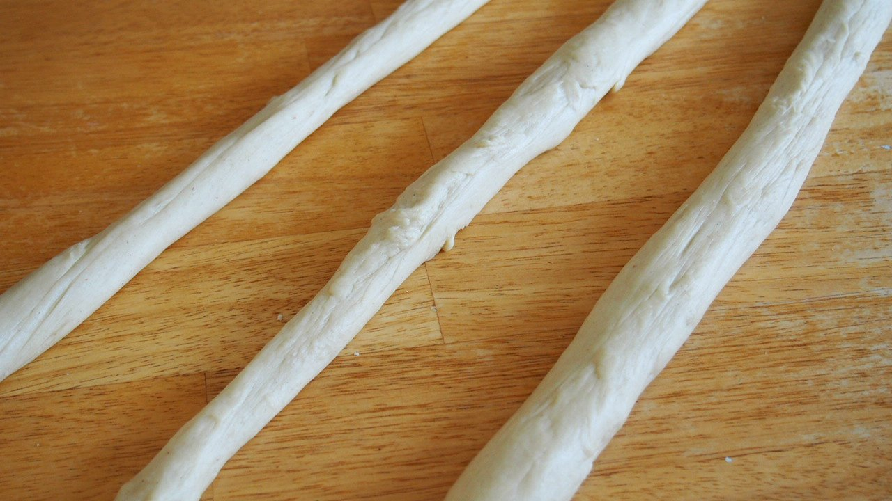 Finnish Pulla bread dough divided into three portions and rolled into ropes.