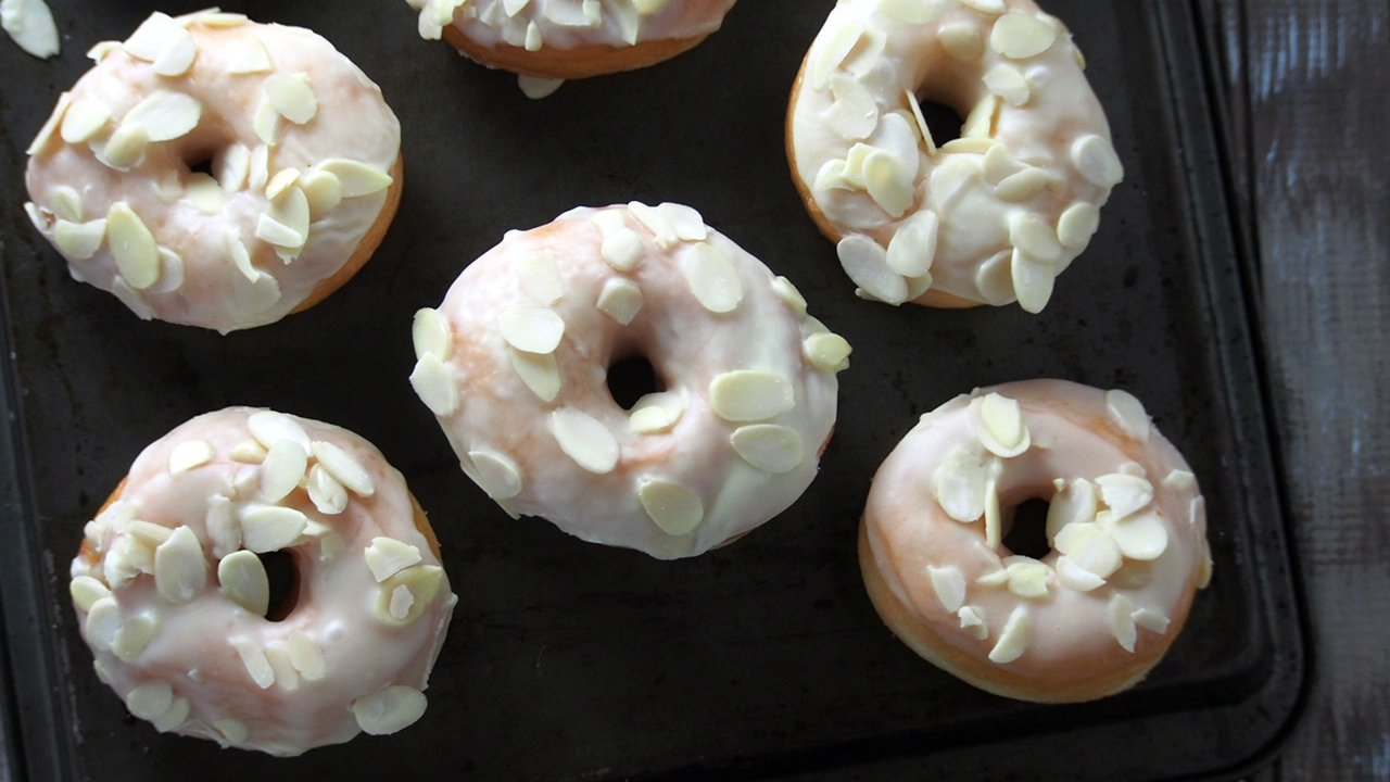 Soft, airy and light yeast donuts are delicious treats especially when glazed with luscious white chocolate and topped with crunchy almond slices.