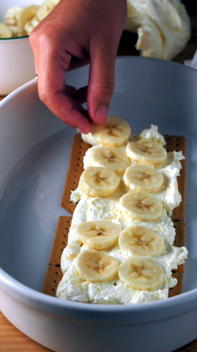 The whipped cream mixture piped onto the graham layer, and the bananas are arranged across the surface.