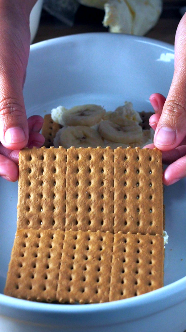 The second layer of graham crackers being arranged on top of the bananas to make the second layer of the banana split icebox cake.