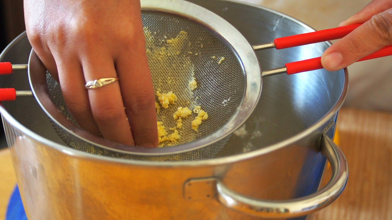Egg yolks being pushed through a fine mesh strainer and into the coarse meal mixture.
