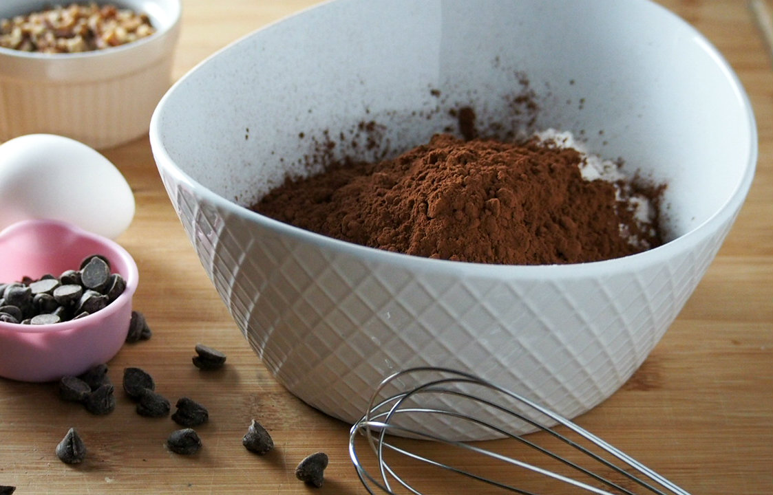 Some of the ingredients for chocolate chip loaf bread-cocoa powder, flour, chocolate chips, and pecan nuts.