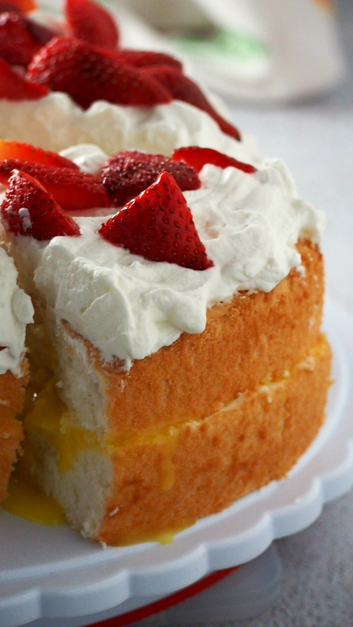 Enjoy this Lemon Angel Food Cake with Lemon Curd Filling- the cottony soft angel food cake is filled with a splash of bright flavor from the lemon curd, then finished with a whipped cream topping.