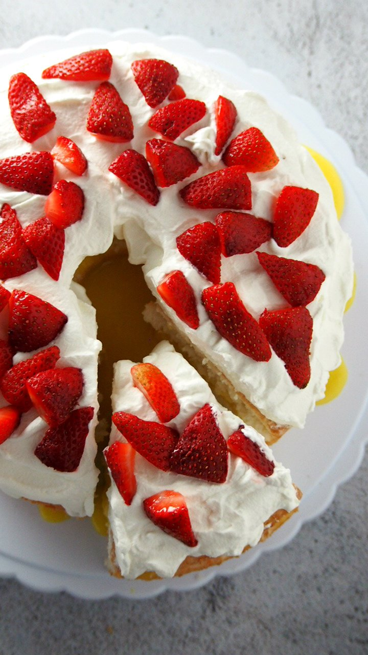 Top angle view of lemon angel food cake with lemon curd filling, with one part sliced.