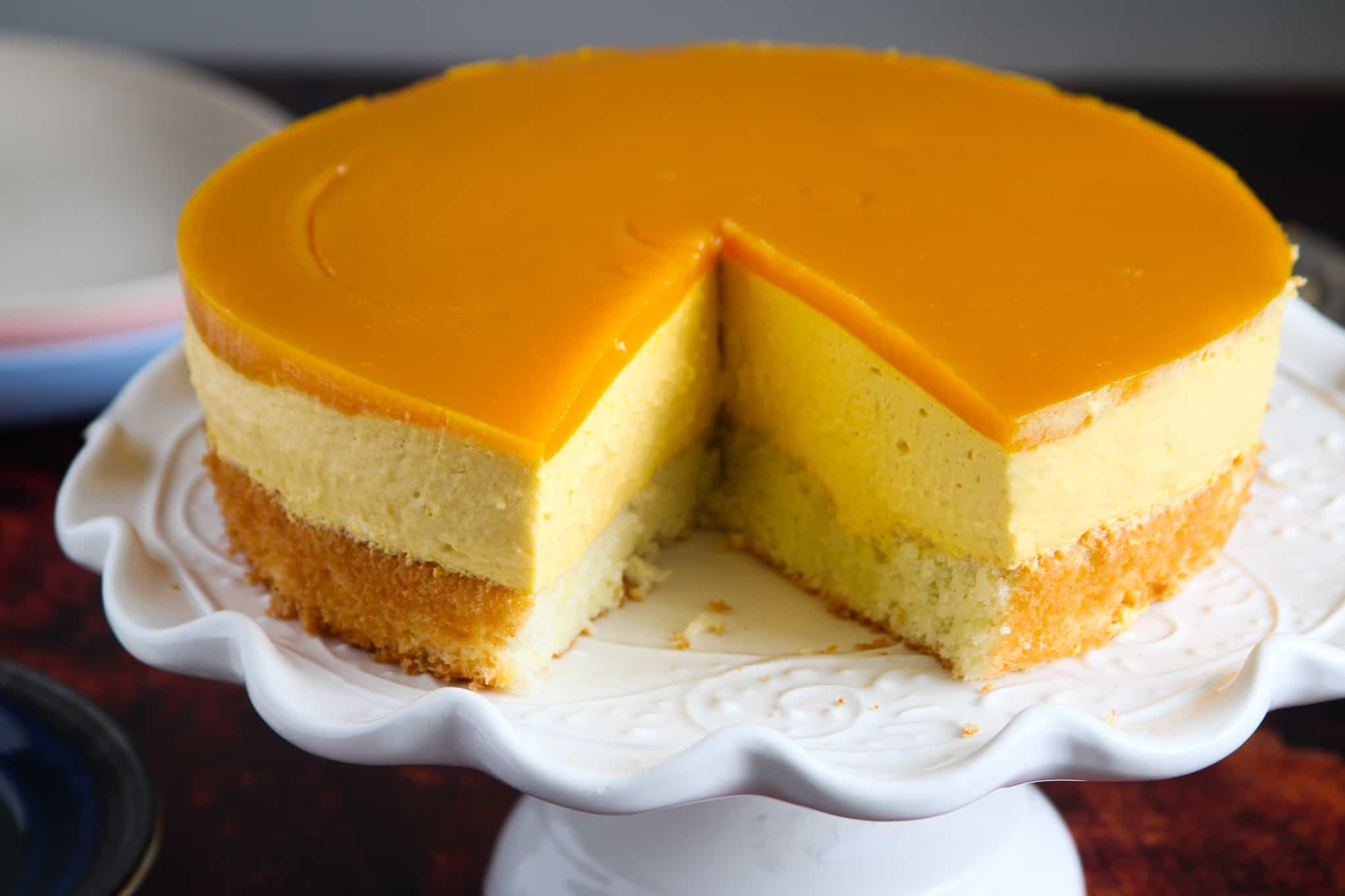 Landscape shot of the mango mousse cake on a cake stand.