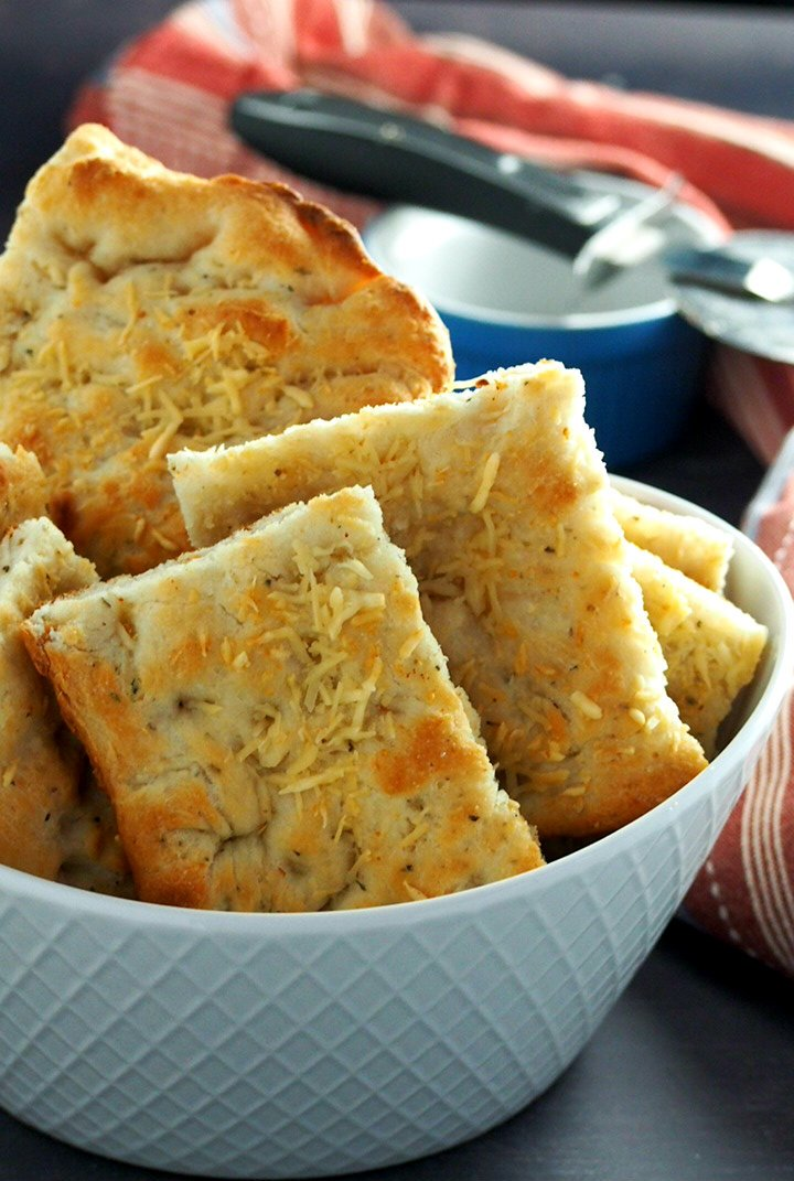 Easy Focaccia bread sliced into rectangles and arranged in a bowl.