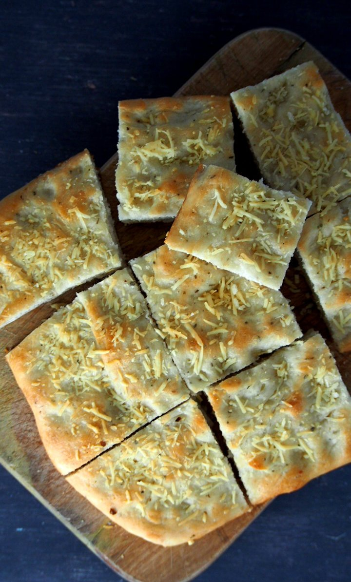 Top angle of easy focaccia bread, sliced in rectangles on chopping board.