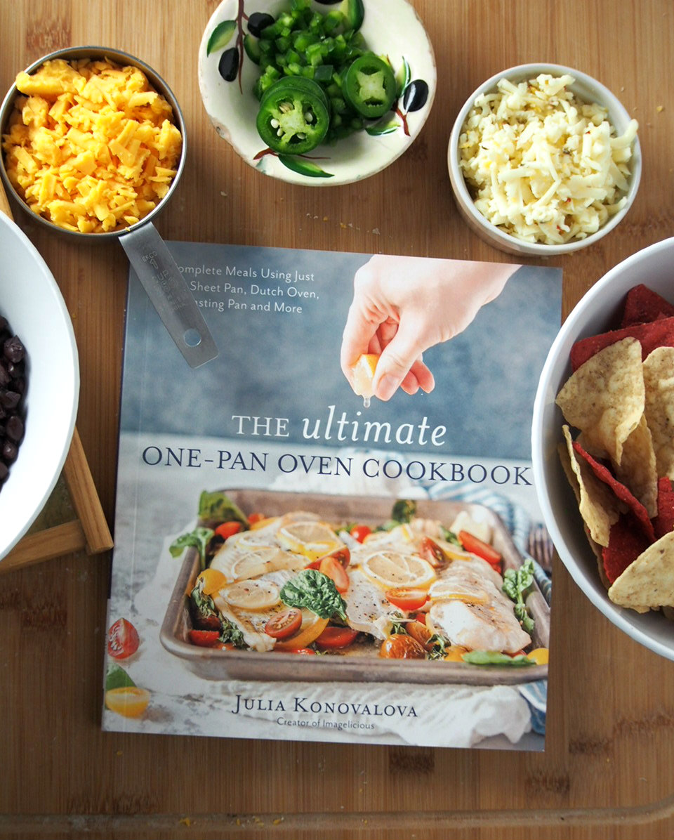 The Ultimate One-Pan Oven Cook Book shown with some of the ingredients of the Bean and Corn Nachos.