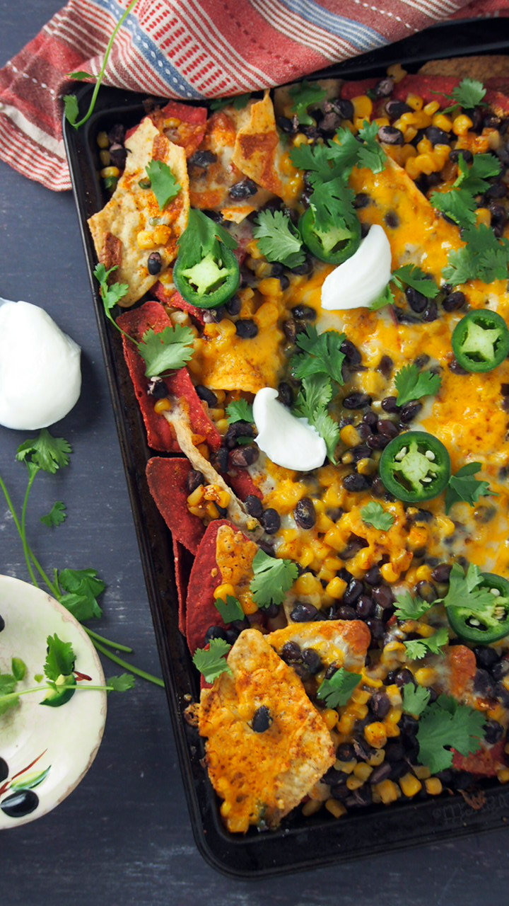 Sheet Pan bean and corn nachos topped with sour cream, jalapeno and cilantro.
