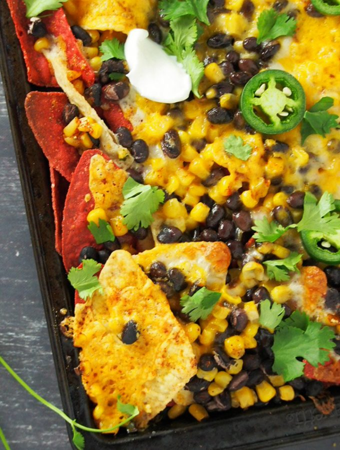 A warm, freshly baked sheet pan bean and corn nachos ready for digging in.