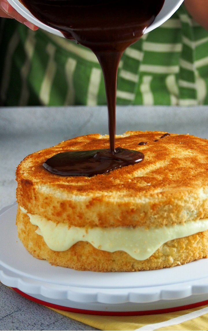 The chocolate glaze being poured on top of the sponge cake to make the Boston Cream Pie.