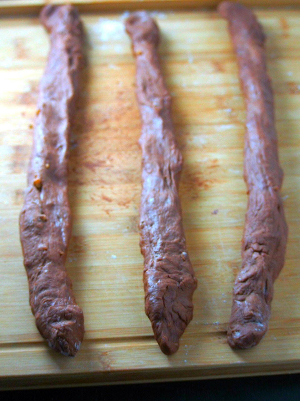 The risen chocolate dough divided into three portions then shaped into 20 inches ropes.