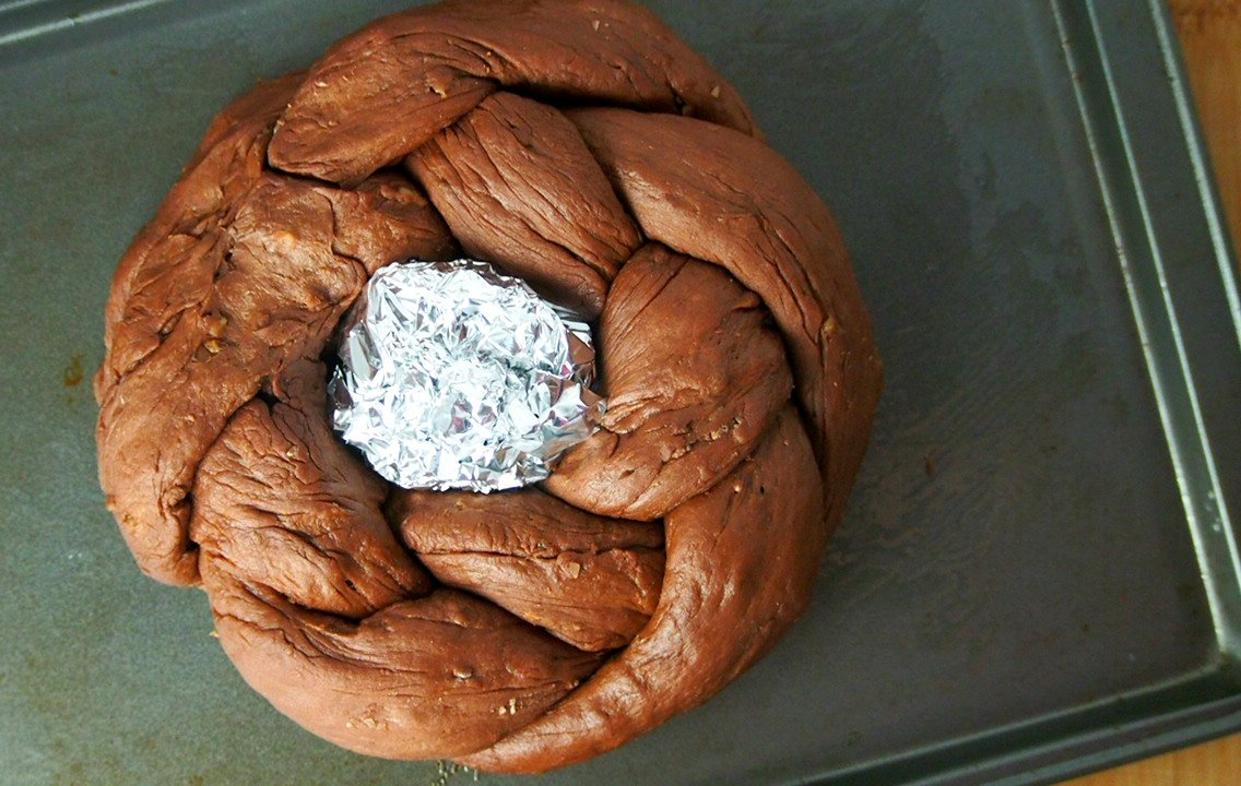 The braid is shaped into a circle, forming a wreath. A ball of foil is placed in the center to retain the shape.