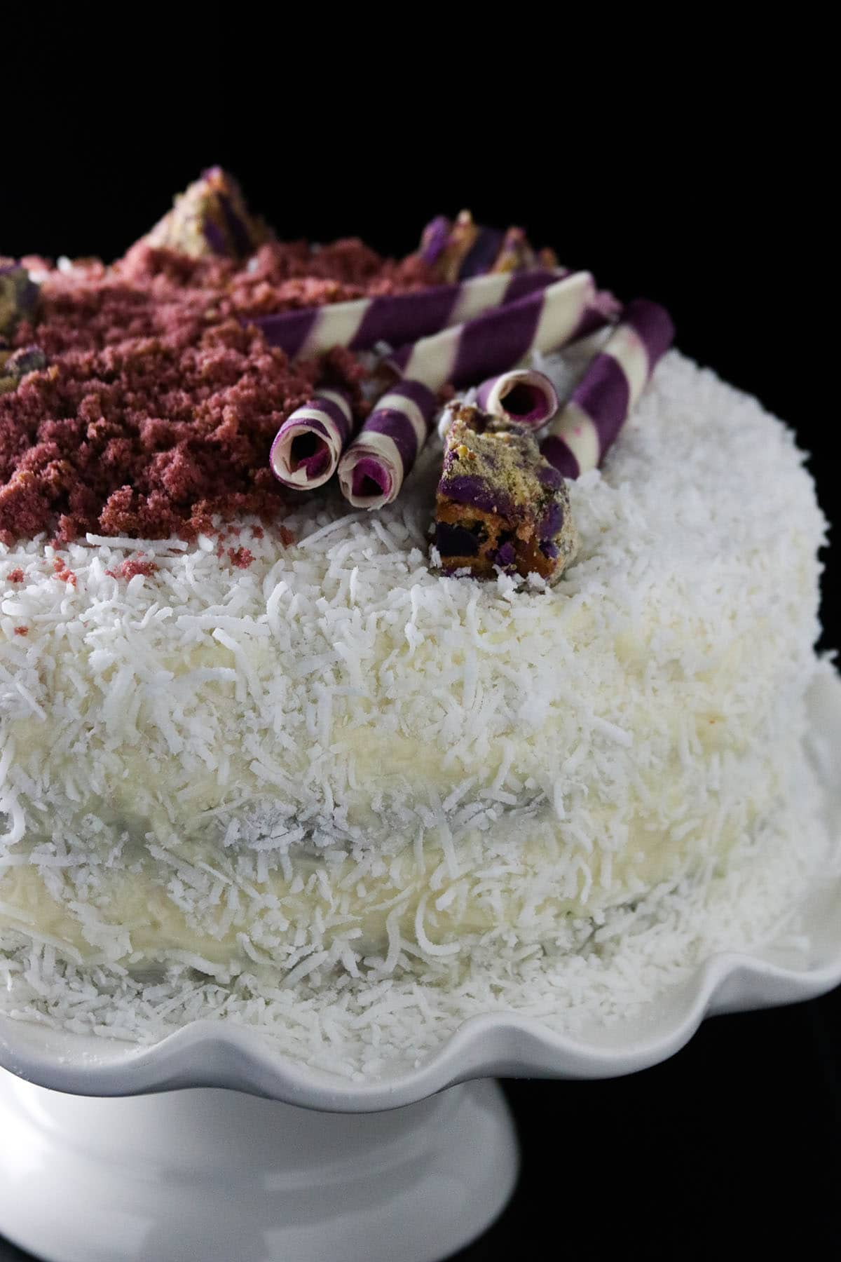 Ube cake with white chocolate on a cake stand.