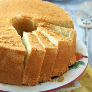 Vanilla Chiffon Cake on a serving plate with some part sliced.