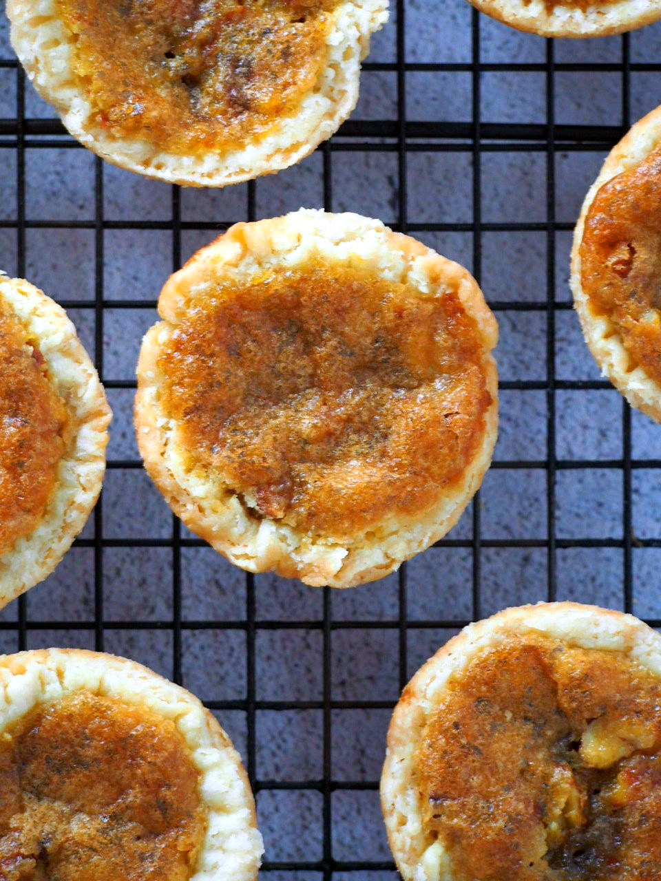 Close up view of a butter tart on a cooling rack.
