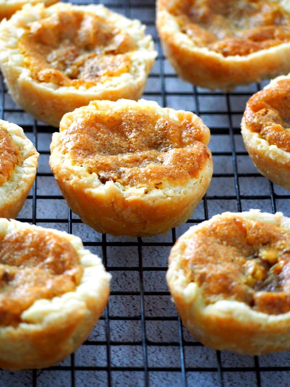 Closer view of butter tarts on a wire rack.