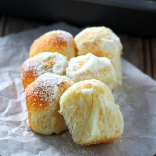 A few pieces of the milk and sugar mini buns on a parchment paper.