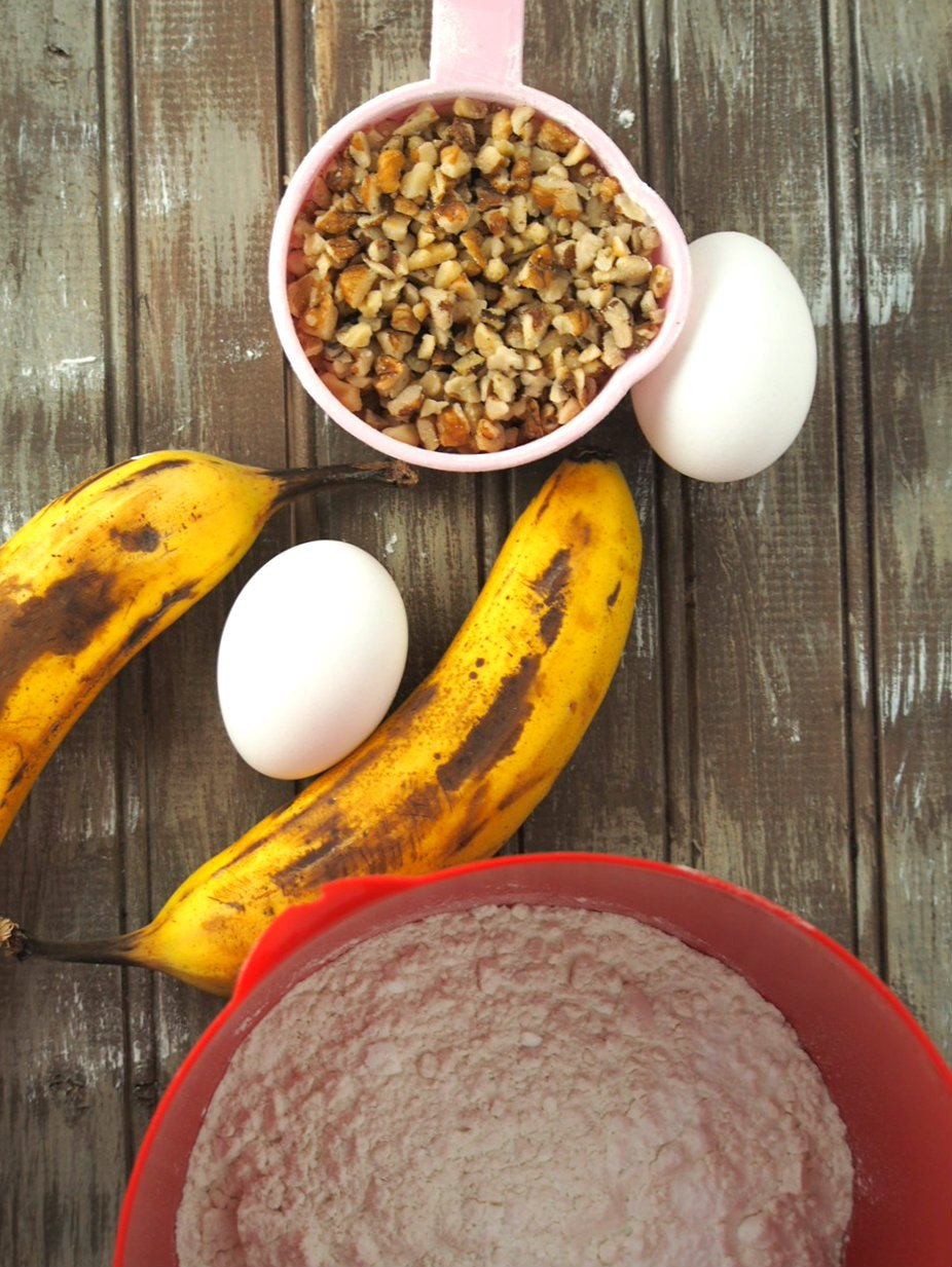 Some of the ingredients for Banana Bundt cake: bananas, walnuts, flour,cocoa powder and eggs.