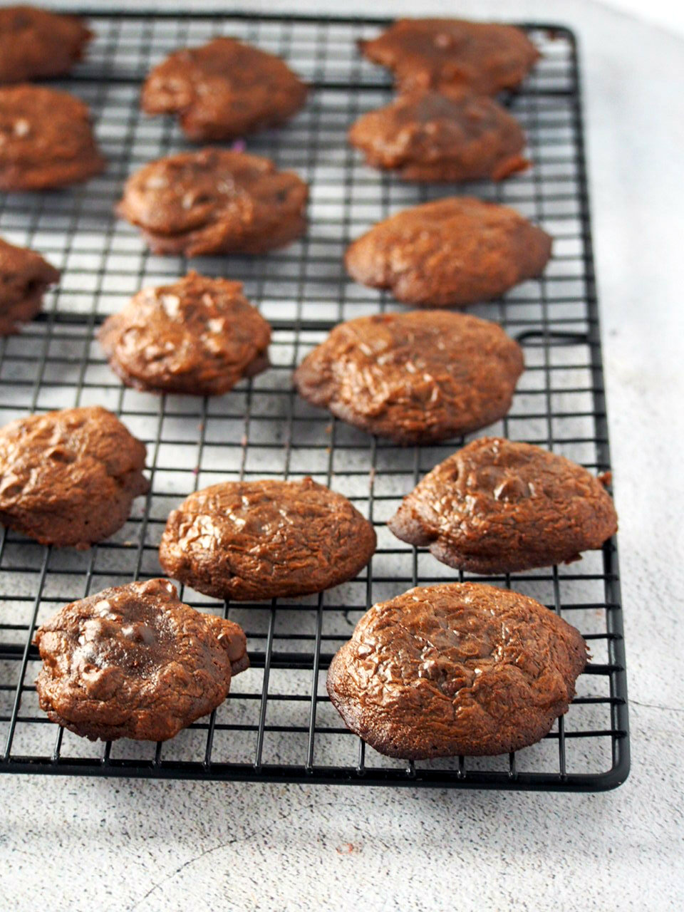Freshly baked brownie cookies cooling on a wire rack.