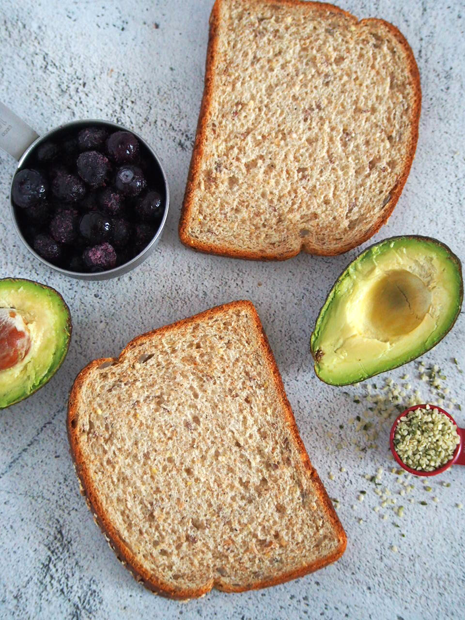 Whole wheat bread slices, avocado, and blueberries for making breakfast toasts.