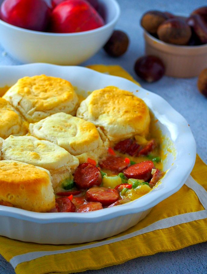 Smokies and veggies pot pie in a pie plate, revealing the filling inside.