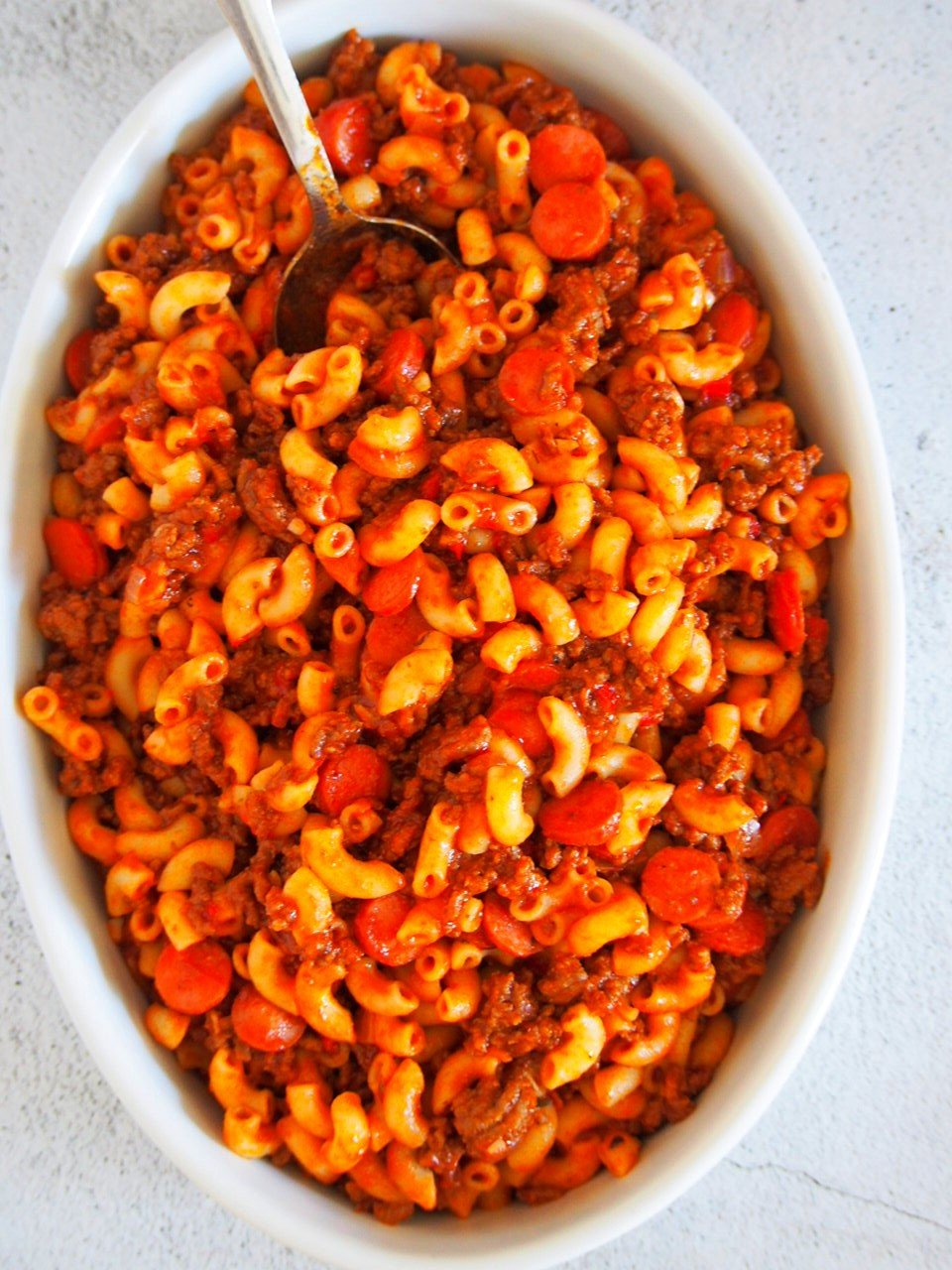 Macaroni and meat sauce tossed together in a dish, waiting for the topping of cheese sauce.