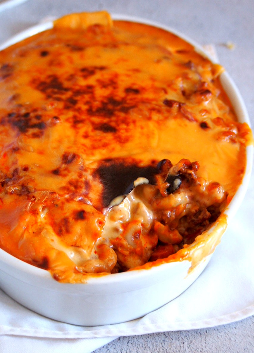 Cheesey baked macaroni with a scooped part, showing the inside pasta and meat sauce.