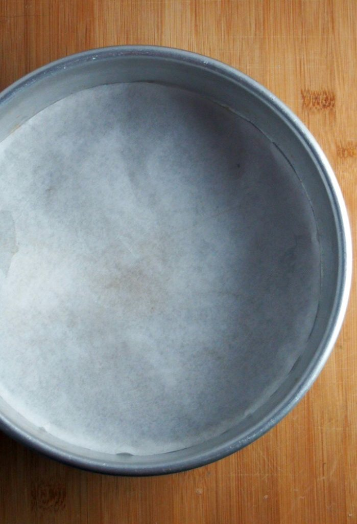 A 9-inch cake pan that is lined with parchment paper.