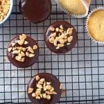 Peanut butter cupcakes on a wire rack, glazed with chocolate and top with peanuts.
