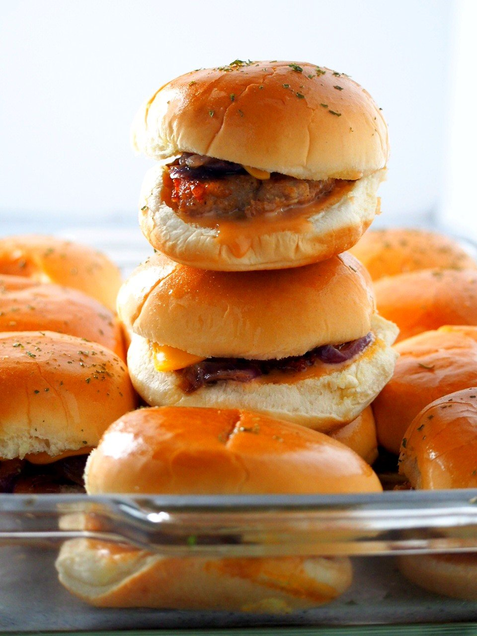 Chicken Burger Sliders stacked and lined up in a baking dish.