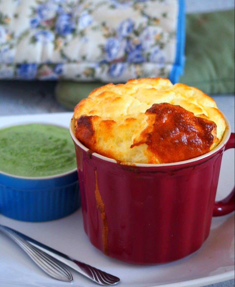 One mug of goat cheese souffle and a creamed spinach sauce on the side.